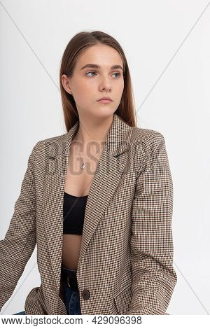 Portrait Of Young Caucasian Attractive Woman With Long Brown Hair In Black Top And Suit Jacket On Wh