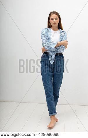 Portrait Of Young Attractive Caucasian Woman With Long Brown Hair In Shirt And Blue Jeans Isolated O