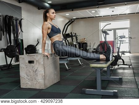 Young Athletic Woman Practicing Reverse Push-ups On Triceps On Benches In Gym