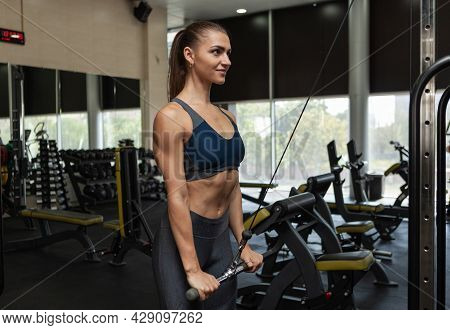 Athletic Woman Training Her Triceps In Cable Crossover Exercise Machine In The Gym