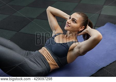 Crunches For The Abdominal Muscles. Young Fit Woman Trains Abdominal Muscles Lying On The Mat In The