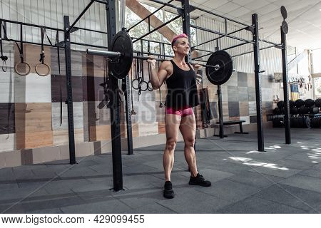 Portrait Of Young Muscular Woman Athlete With Barbell On Her Shoulders In Modern Cross Gym. Sport, F