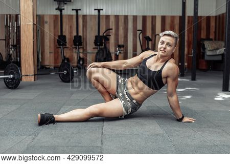 Tired Muscular Woman Athlete Resting While Sitting On The Floor In The Gym