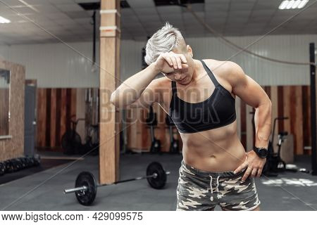Portrait Of Tired Muscular Athletic Woman In The Gym