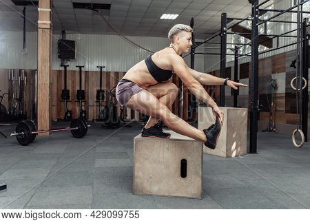 Athletic Woman In Sportswear Doing Squat And Training Legs While Standing On Wooden Box At Gym. Cros