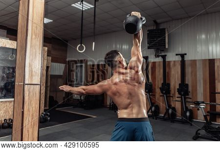 Muscular Powerful Man Exercising With Heavy Kettlebell In Cross Fit Gym. Functional Training With Fr
