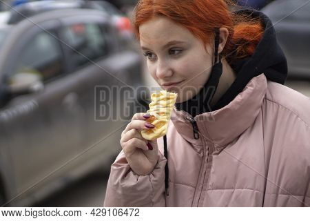 The Girl Eats Flour. The Girl Is Eating A Sweet Cake On The Street.