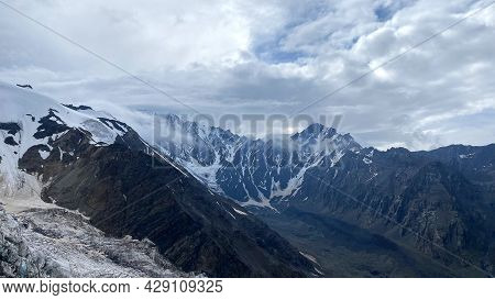 Snow-capped Mountains And Inaccessible Rocks, Blue Sky And White Clouds. Mountain Landscape Of North