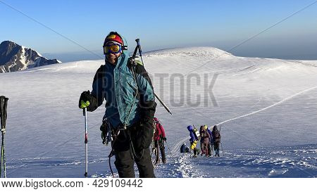 Happy Climbers Go Uphill. Mountain Landscape Of North Ossetia. Snow-capped Mountains. Climbing Kazbe