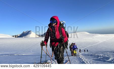 A Climber In A Ski Mask Goes Up The Hill. Mountain Landscape Of North Ossetia. Snow-capped Mountains