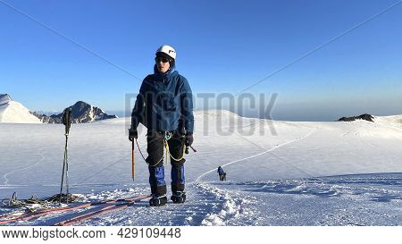 A Climber Walks Along A Snowy Mountain Path. Snow-capped Mountains. Mountain Landscape Of North Osse