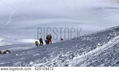 Climbers Climb The Mountain Along A Snowy Path. Mountain Landscape Of North Ossetia. Climbing Kazbek
