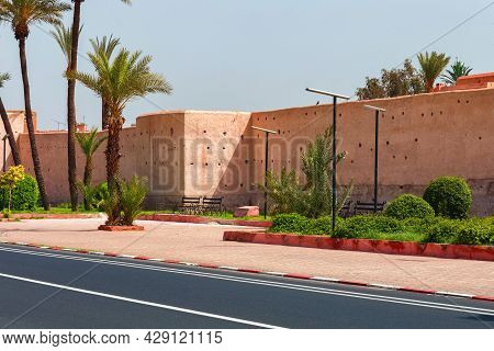 Part Of The Red Medieval Walls Around An Old Historic Area In Marrakech On A Sunny Day. Morocco.