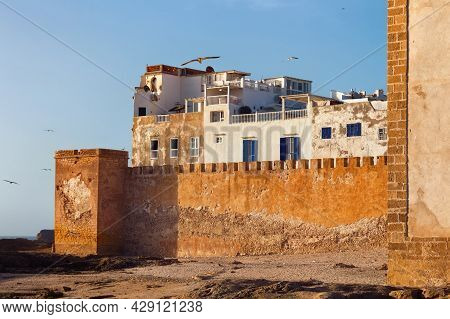 View Of The Historical Walls Of The Essaouira Fortress Near The Volcanic Shore Of The Atlantic Ocean