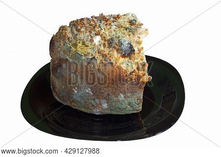 Mouldy Piece Of Bread On Dark Plate, Isolated Obver White Background