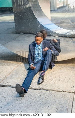 A Young Black Businessman Is Sitting On The Ground, Leaning Against A Modern Mirror Wall, Checking M
