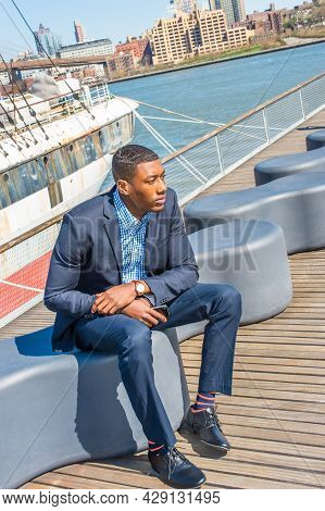 Dressing In A Blue Suit, Leather Shoes, Holding A Mobile Phone, A Young Black Businessman Is Sitting