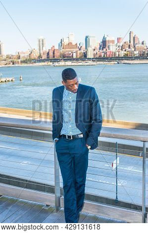 Two Hands Putting In Pockets, Lowering His Head, A Young Black Businessman Is Standing By The River
