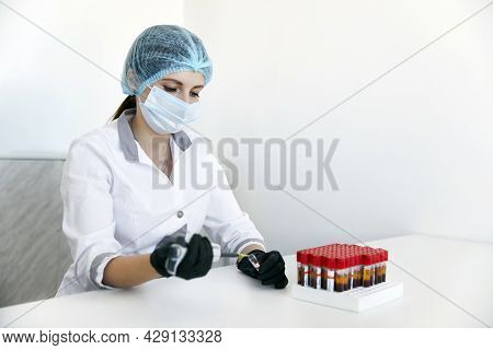 Lab Technician With Tube Of Blood Sample And Rack With Other Samples. Lab Technician Holding Blood T
