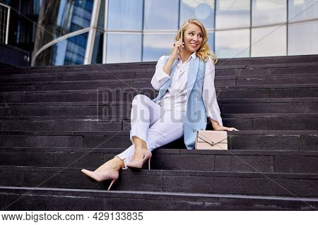 Happy Woman In Business Suit Talks By Cellphone On Stairs.
