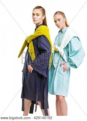 Fashion models girls pose in stylish clothes from the spring-summer collection. Full length studio portrait on a white background. Haute couture clothing.