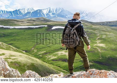 Back View A Man With A Backpack Tourist Climber Stands On The Top Of The Mountain And Looks At The V