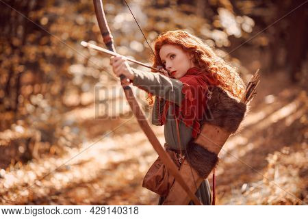A beautiful red-haired girl archer of the Middle Ages aiming with a bow in autumn forest. Celtic culture. Fantasy world.