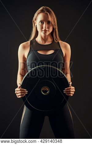 Portrait  of a beautiful sportive brown-haired young woman posing in black clothes holding iron disk on black background. Studio fashion shot.