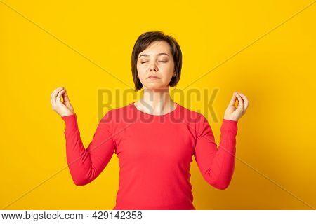 Mindful Peaceful Woman Meditates Indoor, Keeps Hands In Mudra Gesture, Has Eyes Closed, Tries To Rel
