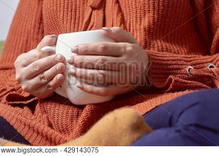 Autumn Mood. Young Female In Orange Woolen Pullover Drinking Refreshing Coffee In A Cold Autumnal Mo
