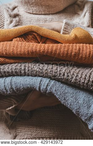 Cropped Shot Of A Female Holding Knitted Warming Sweaters. Preparing Clothes For Coming Cold Season.