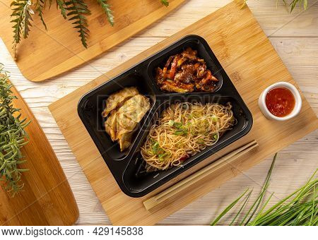 Flat Lay Of Noodles With Beef Stew And Drumplings In Take-out Box On Bamboo Chopping Board