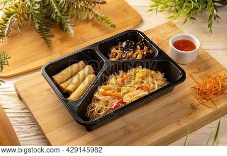 Noodles With Chicken Stew And Spring Rolls In Take-out Box On Bamboo Chopping Board