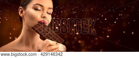 Beautiful young woman eating dark chocolate. Beauty model girl enjoying her chocolate bar, close eyes. Pretty  brunette female biting chocolate bar over brown background, close-up portrait. Enjoyment.