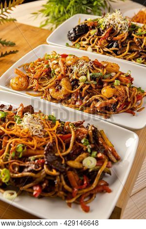 Spicy Chinese Stir Fry Noodles. Three Portions Of Asian Food.