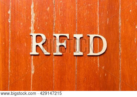 Alphabet Letter In Word Rfid (abbreviation Of Radio-frequency Identification) On Old Red Color Wood