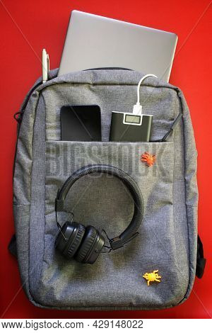 Modern Laptop Backpack With Gadgets: Headphones, Smartphone, Laptop And External Battery. Red Backgr
