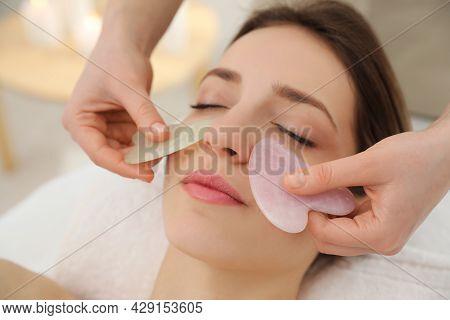 Young Woman Receiving Facial Massage With Gua Sha Tools In Beauty Salon, Closeup