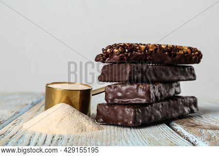 Different Tasty Bars And Scoop Of Protein Powder On Wooden Table