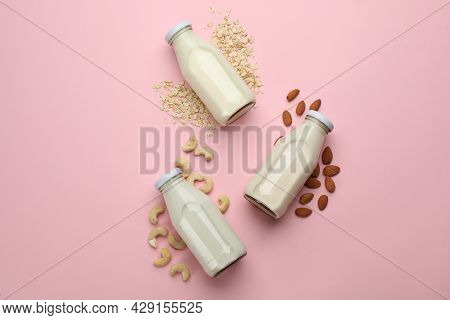 Different Vegan Milks, Oat Flakes And Nuts On Pink Background, Flat Lay