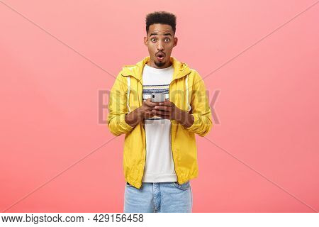Impressed Enthusiastic African American Male With Curly Haircut Folding Lips In Wow Sound Holding Sm