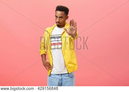 Hold On Not Move. Portrait Of Serious-looking Intense Handsome Dark-skinned Guy In Trendy Outfit Pul