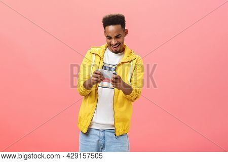 Enthusiastic Guy Having Fun Playing Awesome Smartphone Game Holding Cellphone In Both Hands Staring