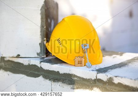 Construction Yellow Hardhat And Key To House On Window Of Housing Made Of Blocks Of Porous Concrete.