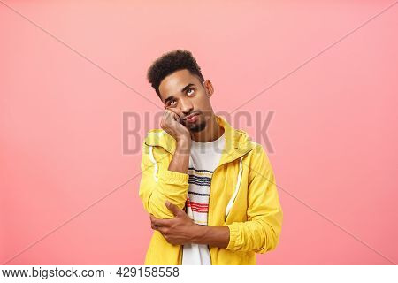 Waist-up Shot Of Bored Irritated African American Man With Beard And Afro Haircut Leaning Head On Pa