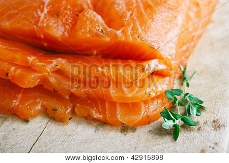 smocked salmon homemade, with spice on wooden board, shallow dof