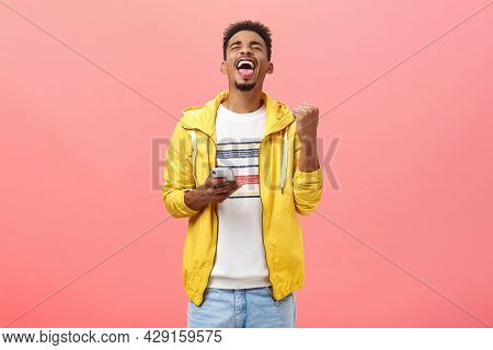 Pleased Delighted Good-looking African Guy Triumphing Beating Score In Popular Smartphone Game Raisi