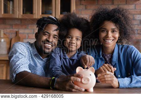 Portrait Of Happy Family With Kid Saving Money