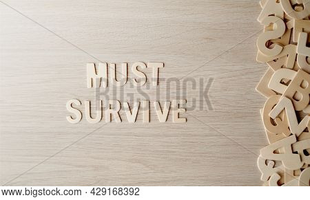 The Word Must Survive, Wooden Letters On A Wooden Table, Top View.
