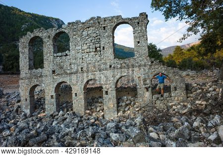 Alakilise ruins along Lycian way hiking trail, Male tourist stands on wall remains of Alakilise or Church of the Angel Gabriel in Lycia, near Finike and Demre, Antalya Province, Turkey